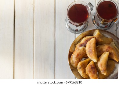 Qatayef Served with Tea from Above on White Wooden Table with Copy Space Left