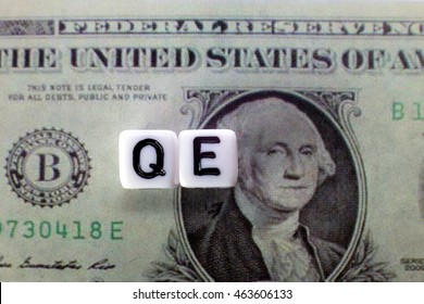 QE written on cube with dollars background for quantitative easing concept.
