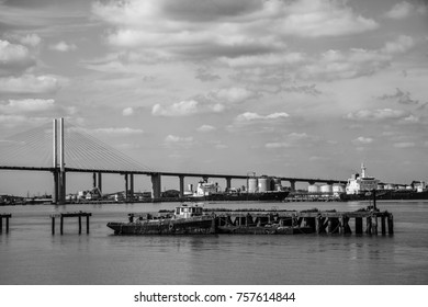 QEII Bridge over the River Thames with barges in foreground, mono