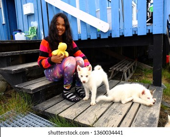 Qeqertarsuaq / Greenland - 16th July 2015: Inuit girl with two puppies of Greenlandic dog