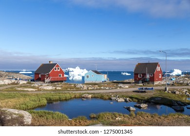 Qeqertarsuaq, Greenland - July 05, 2018: Colorful wooden houses with icebergs in the background