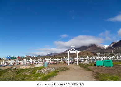 Qeqertarsuaq, Greenland - July 6, 2018: White wooden crosses and artificial flowers on the traditional cemetery
