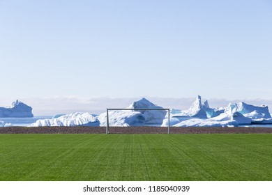 Qeqertarsuaq, Greenland - July 6, 2018: The soccer field with icebergs in the background