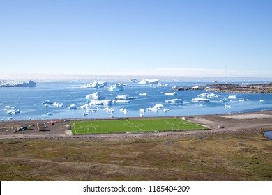 Qeqertarsuaq, Greenland - July 6, 2018: Soccer field with the ocean and icebergs in the background