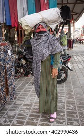 Qeshm, Iran - December 21, 2015: Bandari woman wearing a traditional mask called the burqa, Qeshm Island, Salakh, Iran