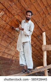 Qeshm, Iran - October 22, 2015 : Afghan worker building a traditional wooden vessel in Qeshm shipyard, Persian Gulf