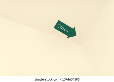 A Qibla arrow sign for a Muslim prayer direction