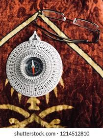 Qibla and eyeglass on pray mat