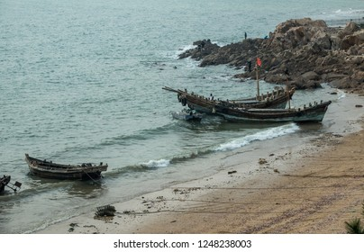 QINGDAO, CHINA - 23 OCTOBER 2018: Traditional fishing boats unload catch on beach in Qingdao in China