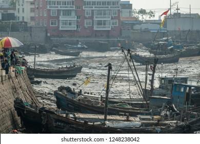 QINGDAO, CHINA - 23 OCTOBER 2018: Traditional fishing boats await tide in Qingdao in China