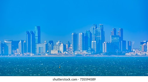 """QINGDAO, CHINA - Jan 20, 2017: Twilight skyline of chinese city Qingdao, known as a """"Pearl on the Yellow Sea""""."""