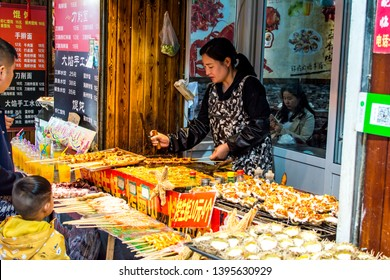 QINGDAO, SHANDONG, CHINA - MAY 11, 2019: A stall selling freshly made seafood cuisine in Pichai Yuan (Literally Firewood Courtyard), a famous food street in Qingdao downtown.