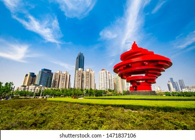 """QINGDAO, SHANDONG, CHINA - MAY 11, 2019: """"May Fourth"""" Wind sculpture in May Fourth Square with Qingdao downtown skyscrapers in the background"""