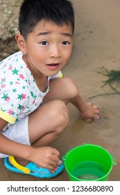 Qingdao, Shandong Province / China - August 6th 2015: Chinese boy playing in the sand, beach of Qingdao, China