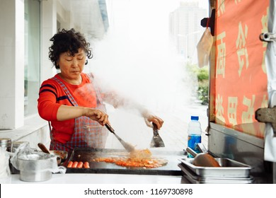 Qinhuangdao, Hebei / China - August 30, 2018. Street food. Chinese woman cooking street food. Life and travel in China