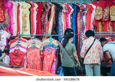 Qipao, cheongsam, or Chinese National dress sell on the street at China Town. People look and buy for China New year.