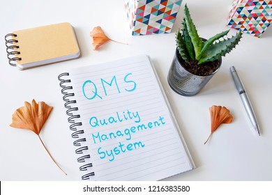 QMS Quality management system written in a notebook on white table