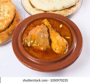 Qourma Salan, Indian food, Top view of Chicken Qorma dish with cardamom and Naan or sheermal on white background, Ramzan iftar meal, Ramadan dinner.