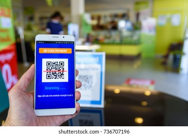 QR code payment, cashless technology concept : Man's left hand holds a touch screen smartphone scans QR code to pay money in a retail shop. QR code is a matrix barcode stores informations of an item.