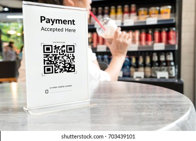 Qr code payment , online shopping , cashless technology concept. Coffee shop accepted digital pay without money , plastic tag on table.