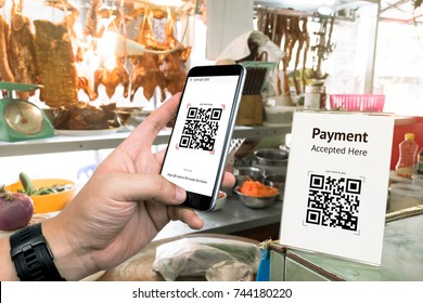 Qr code payment , online shopping , cashless technology concept. Restaurant in market accepted digital pay without money , plastic tag on table and hand using mobile phone application to scan qr code.