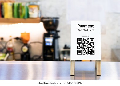 Qr code payment , online shopping , cashless society technology concept. Coffee shop accepted digital pay without money , wood stand tag on table.