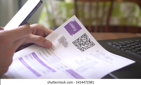 QR Code Payment. Utility Billing Online. Payment of utilities using QR code and mobile device. A man scanning the QR code with app and paying utility bills using his smartphone