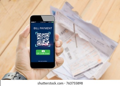QR CODE scanning concept.Hands holding mobile phone on blurred utility bill on wooden table as backgrounds