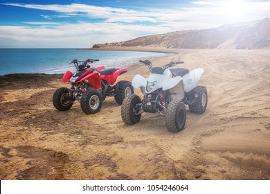 Quad ATV all terrain vehicle, parked on beach, red and white motor bikes ready for action, with summer sun flaring on bright day, outdoor extreme activity adrenaline sport, racing, San Felipe, Mexico