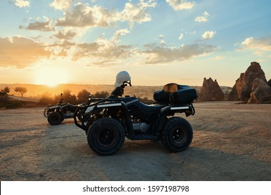 Quad ATV parked on sand without drivers on sunset background in Cappadocia Turkey