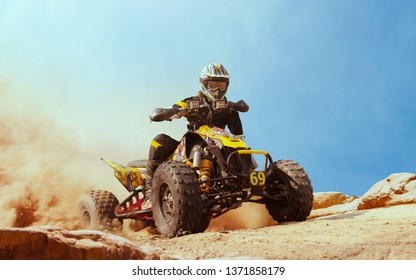 Quad bike in dust cloud, sand quarry on background. ATV Rider in the action.