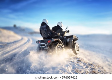 Quad bike in motion, ride on top of the mountain on snow. People riding quad bike on mountain at sunset