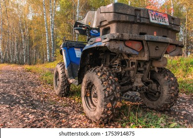 Quad bike on the road. A blue ATV POLARIS Quad bike stands on the road in the autumn forest. The SUV is covered in dirt close-up view from the back. Russia, Krasnoyarsk territory, September 23, 2016