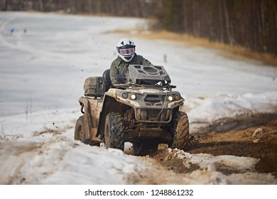 Quad bike rides on a snowy field, against of  winter forest. Outdoor activities on the ATV