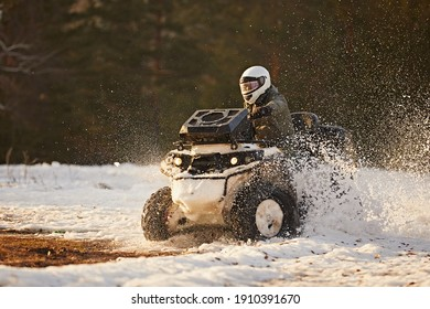 Quad bike rides on a snowy field, raising a bunch of splashes, against the backdrop of a bright winter sunset. Outdoor activities on the ATV