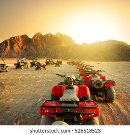 Quad bikes in desert at the sunset