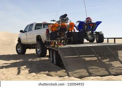 Quad bikes on trailer in desert