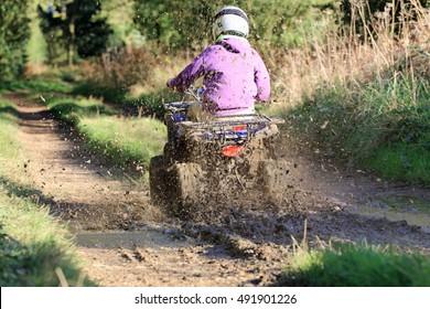 Quad biking down a countryside farm track. Dirty water splash.