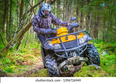 Quad biking. A stressful man rides a quad bike through the mud. Off-road riding on ATV. Turn on abyss on the ATV. Active sports. Extreme. Quad bike rental.