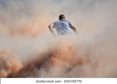 Quad dirt bike rider obscured by dust cloud. Extreme sports