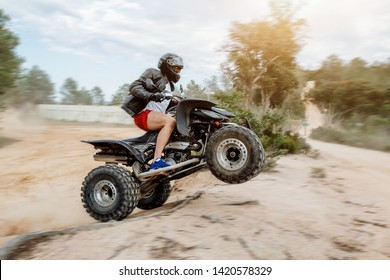 The quad racer is jumping on the dusty road. Quad bike off-road. Quad bike in action.