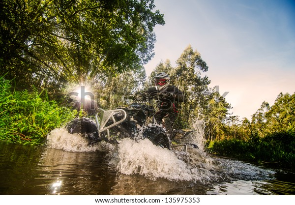 Quad rider through water stream in the forest against sunlight.