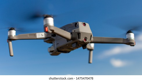 Quadcopter drone with the camera against the blue sky. Close-up