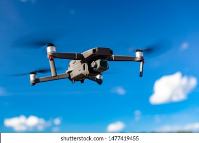 Quadcopter drone flying over blue sea. New technology in the aero photo shooting.