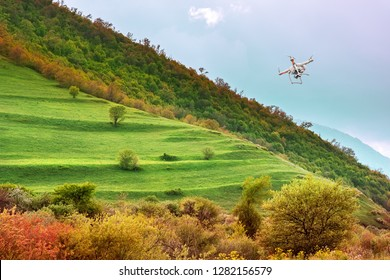 Quadcopter flies over the hill. White drone hovering in a bright blue sky. New technology in the aero photo shooting.