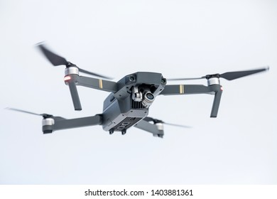 the quadcopter of gray color with the camera in flight against