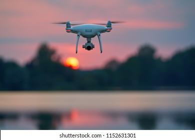 Quadcopter model hovering over lake against blurred red setting sun in background.