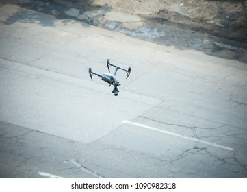 Quadcopter UAV`s Drone for commercial aerial photography flying over old motorway examines the defects of the road surface.