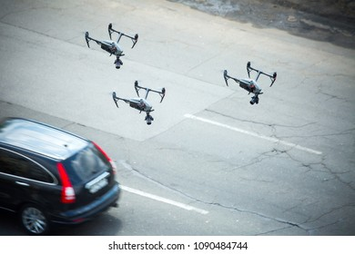 Quadcopter UAV`s drones for commercial aerial photography fly over motorway, at caught up with the pursuit keeps track of a car.