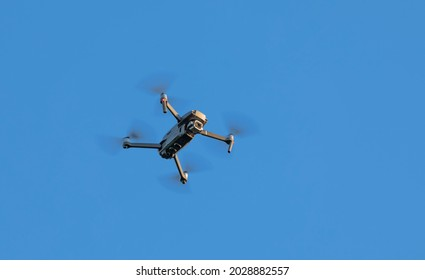 Quadcopter with video camera on a background of blue sky, bottom view. Concept, observation and shooting with a drone.